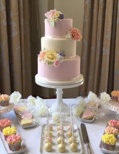 pastel wedding cake with cupcakes cookie and sweetie jars