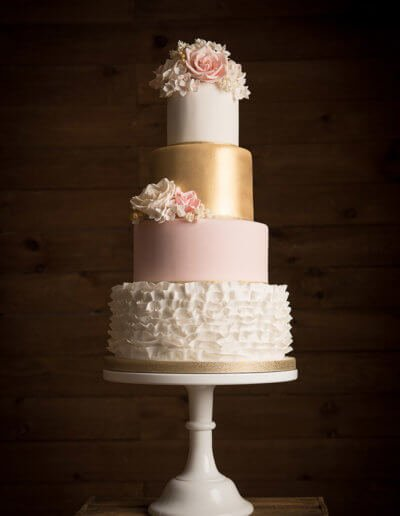 Blush ruffles and gold wedding cake